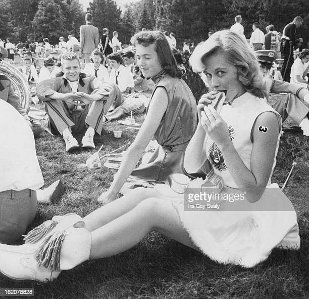 SEP 26 1958 SEP 28 1958 Petite Mavis Doetz Littleton High School majorette gives the photographer a sidelong glance as she munches a hotdog on the CU...