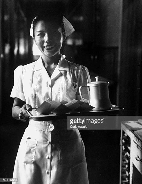 A petite young nurse in uniform smiling at the camera as she is carrying a tray of medicine and water