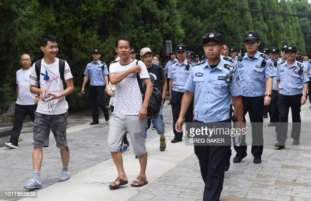 Petitioners are escorted out of a park by police and security personnel before being loaded on buses and driven away in Beijing on August 6 2018...