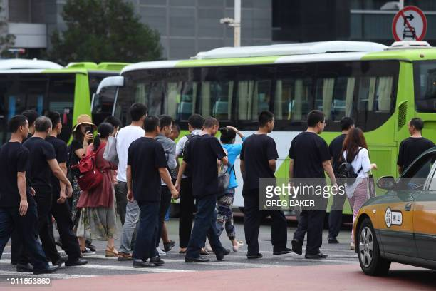 Petitioners are escorted to a bus by security personnel before being driven away in Beijing on August 6 2018 Hundreds of police swarmed the streets...