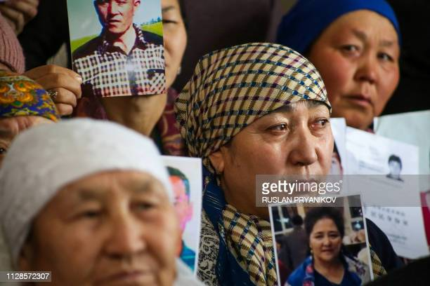 Petitioners with relatives missing or detained in Xinjiang hold up photos of their loved ones during a press event at the office of the Ata Jurt...