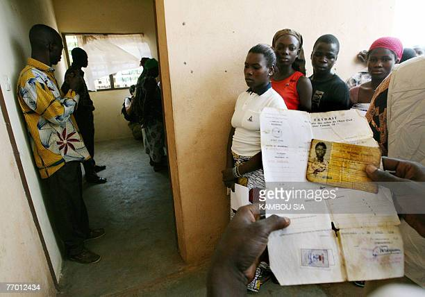 A petitioner's witness holds her identification card and her birth certificate as young women wait in line to see a doctor to determine their age 25...