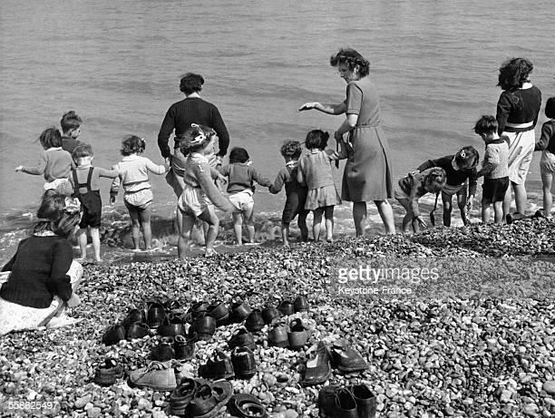 Petits vacanciers londoniens qui découvrant la mer pour la première fois mettent les pieds dans l'eau à Kingsdown dans le Kent au RoyaumeUni circa...