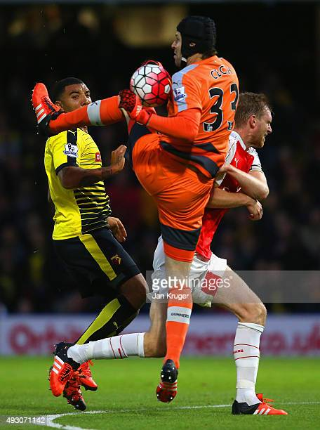 Petr Cech of Arsenal attempts to clear the ball outside the area from Troy Deeney of Watford during the Barclays Premier League match between Watford...