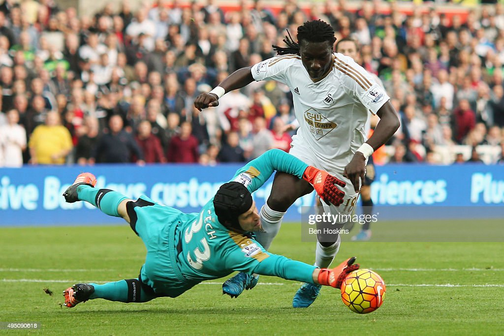 Petr Cech of Arsenal brings down Bafetimbi Gomis of Swansea City during the Barclays Premier League match between Swansea City and Arsenal at Liberty Stadium on October 31, 2015 in Swansea, Wales.