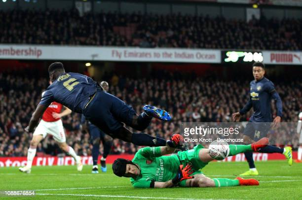 Petr Cech of Arsenal dives to block Paul Pogba of Manchester United from shooting during the FA Cup 4th round match between Arsenal and Manchester...