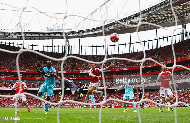 Petr Cech of Arsenal fails to punch clear the ball as Cheikhou Kouyate of West Ham United heads in the opening goal during the Barclays Premier...
