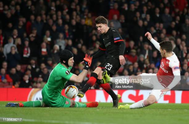 Petr Cech of Arsenal saves a shot from Adrien Hunou of Stade Rennais during the UEFA Europa League Round of 16 Second Leg match between Arsenal and...