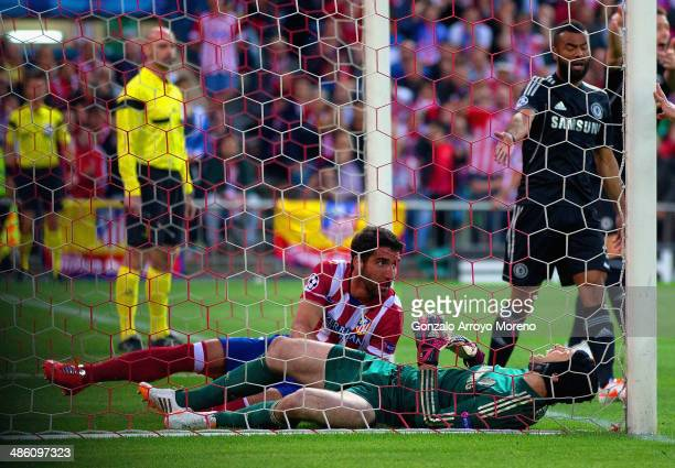 Petr Cech of Chelsea lies injured after clashed with Raul Garcia of Club Atletico de Madrid during the UEFA Champions League Semi Final first leg...