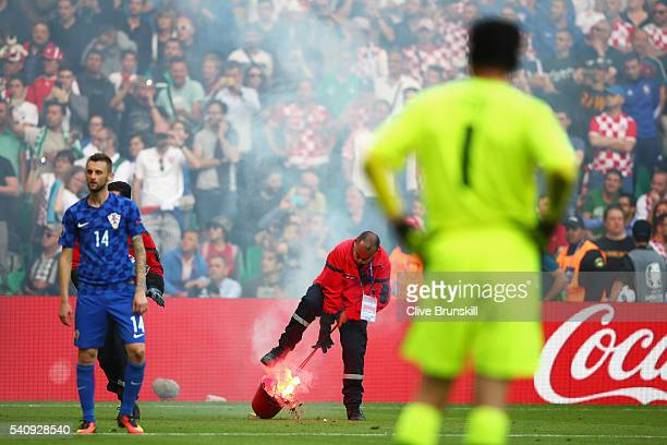 Petr Cech of Czech Republic and Marcelo Brozovic of Croatia look on as a fire marshal removes flares from the pitch during the UEFA EURO 2016 Group D...