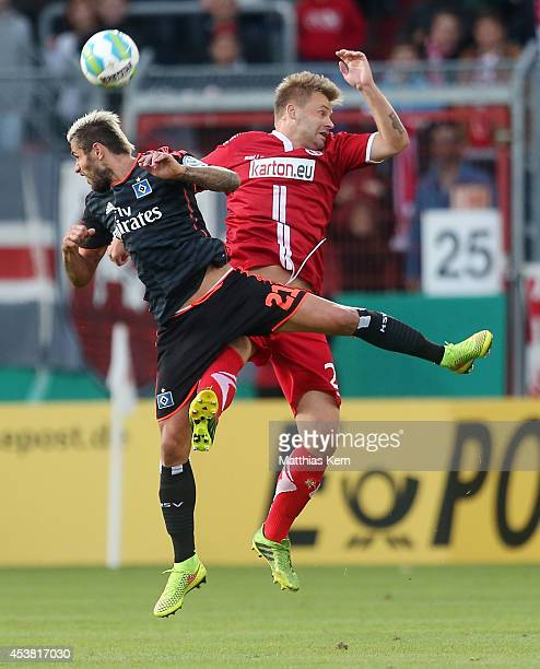Petr Jiracek of Hamburg and Zbynek Pospech of Cottbus jump for a header during the DFB Cup match between FC Energie Cottbus and Hamburger SV at...