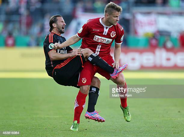 Petr Jiracek of Hamburg is attackt by Zbynek Pospech of Cottbus during the DFB Cup match between FC Energie Cottbus and Hamburger SV at Stadion der...