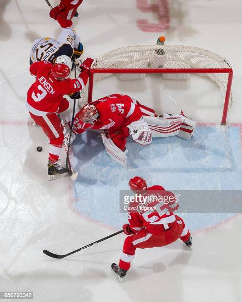 Petr Mrazek Nick Jensen and Niklas Kronwall of the Detroit Red Wings defend the net from Hudson Fasching of the Buffalo Sabres during an NHL game at...
