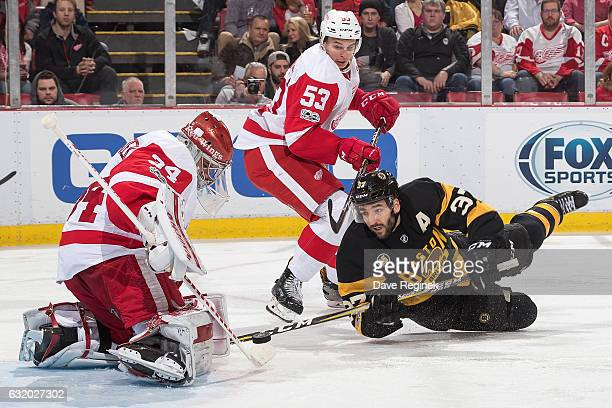Petr Mrazek of the Detroit Red Wings makes a save as teammate Alexey Marchenko defends against Patrice Bergeron of the Boston Bruins during an NHL...