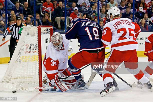 Petr Mrazek of the Detroit Red Wings stops a shot from Ryan Johansen of the Columbus Blue Jackets as Cory Emmerton of the Detroit Red Wings attempts...