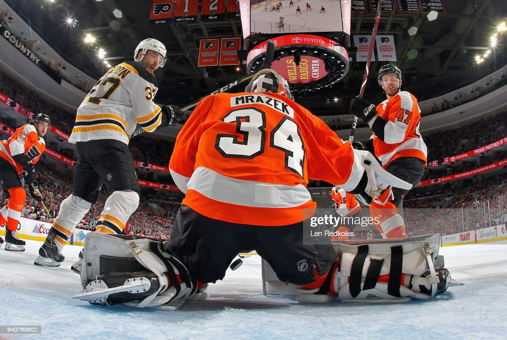 Petr Mrazek #34 of the Philadelphia Flyers lets the puck fall between his pads as Andrew MacDonald #47 and Patrice Bergeron #37 of the Boston Bruins look back into the net on April 1, 2018 at the Wells Fargo Center in Philadelphia, Pennsylvania. The Flyers went on to defeat the Bruins in overtime 4-3.