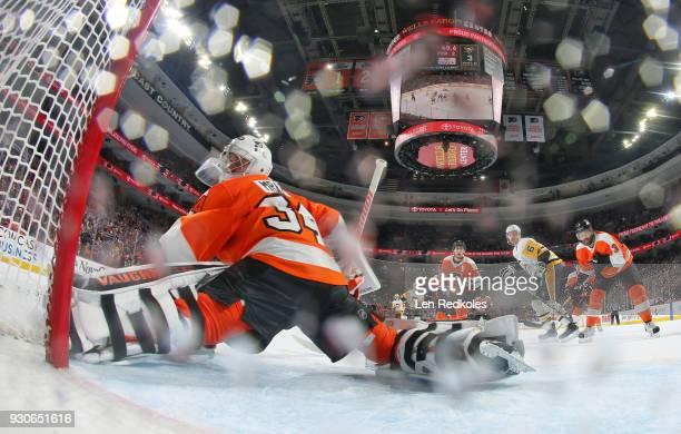 Petr Mrazek Valtteri Filppula and Radko Gudas of the Philadelphia Flyers react to a shot on goal by Jamie Oleksiak of the Pittsburgh Penguins on...