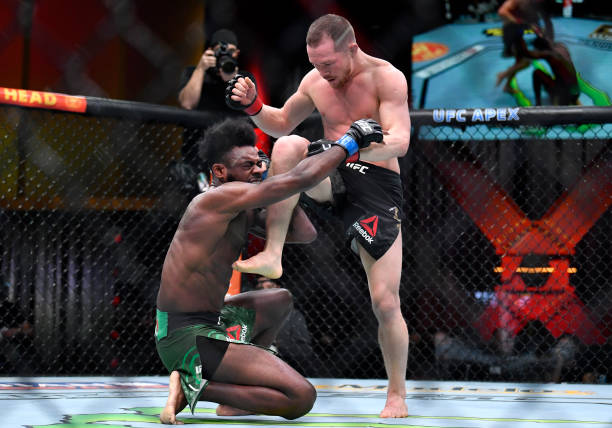 Petr Yan of Russia delivers an illegal knee against Aljamain Sterling in their UFC bantamweight championship fight during the UFC 259 event at UFC...