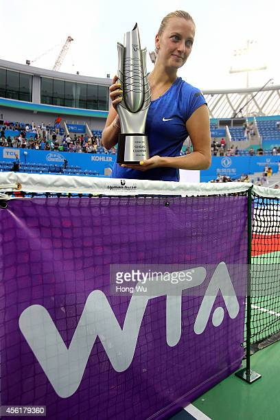 Petra Kvitova of Czech Republic holds the trophy beside WTA logo to celebrate at the award ceremony after winning the final match against Eugenie...