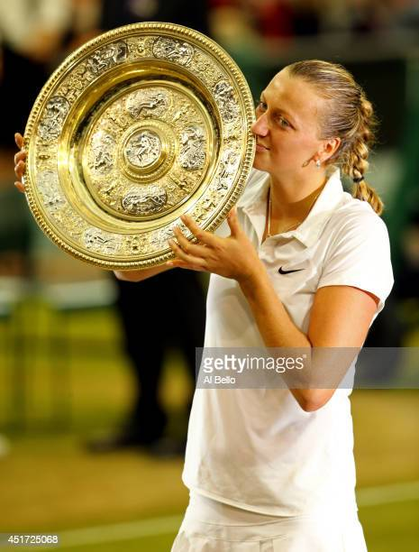 Petra Kvitova of Czech Republic poses with the Venus Rosewater Dish trophy after her victory in the Ladies' Singles final match against Eugenie...