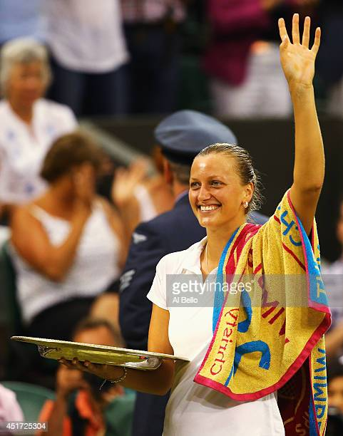 Petra Kvitova of Czech Republic waves to the fans as she stands holding the Venus Rosewater Dish trophy after her victory in the Ladies' Singles...