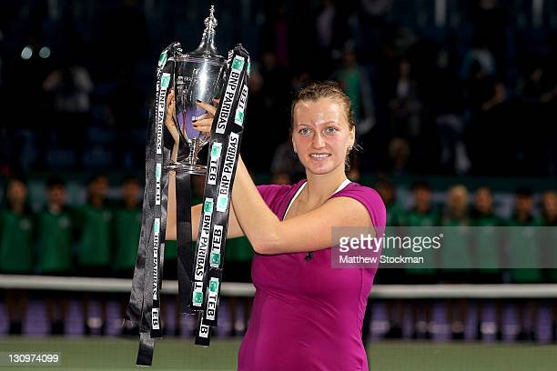 Petra Kvitova of the Czech Republic poses for photogrpahers with the Billy Jean King trophy after defeating Victoria Azarenka of Belarus during the...