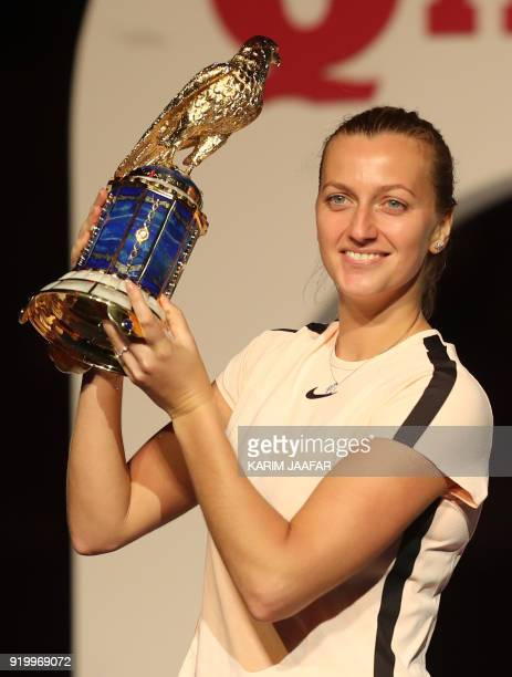Petra Kvitova of the Czech Republic poses with her winning trophy on the podium after beating her opponent Garbine Muguruza of Spain in the final of...
