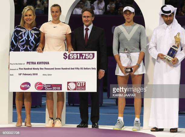Petra Kvitova of the Czech Republic stands with her winning check on the podium between Laurent Wolffsheim Managing Director of Total EP Golfe and...