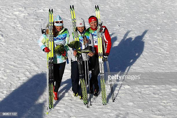 Petra Majdic of Slovenia celebrates winning the bronze medal, Marit Bjoergen of Norway gold and Justyna Kowalczyk of Poland silver during the Women's...