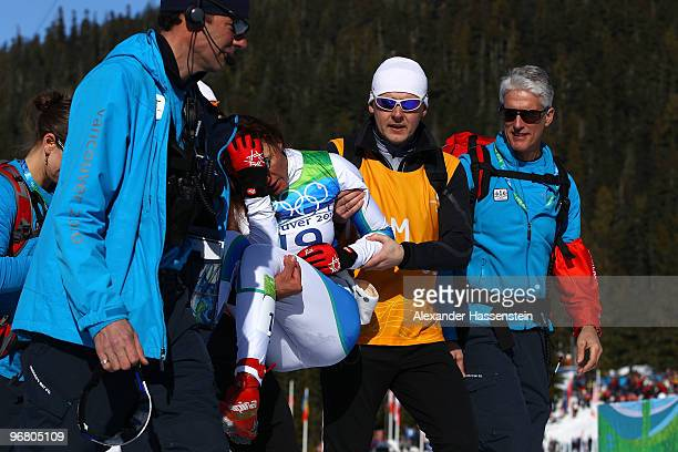 Petra Majdic of Slovenia is assisted is assisted off the course after she was injured while winning the bronze medal in the Women's Individual Sprint...