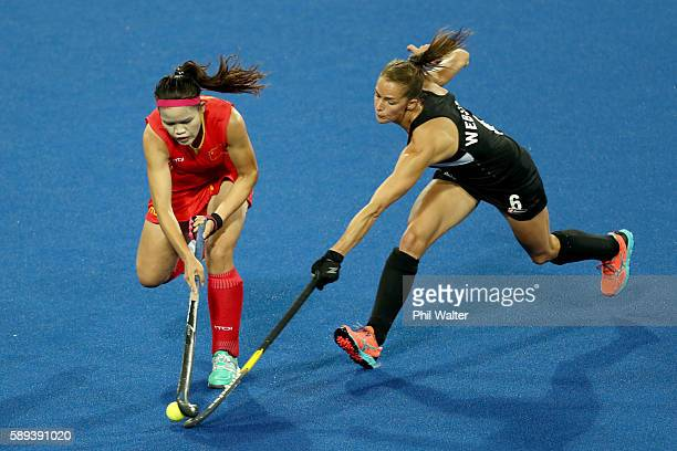 Petrea Webster of New Zealand and Qiuxia Cui of China compete for the ball in the Women's Pool A match between the People's Republic of China and New...