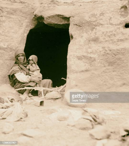 Petrean types, etc. Petra. Bdul troglodyte Arabs. Mother and baby before their cave home in ed-Der Valley. 1920, Jordan, Petra .