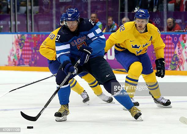 Petri Kontiola of Finland handles the puck against Gabriel Landeskog of Sweden in the first period during the Men's Ice Hockey Semifinal Playoff on...