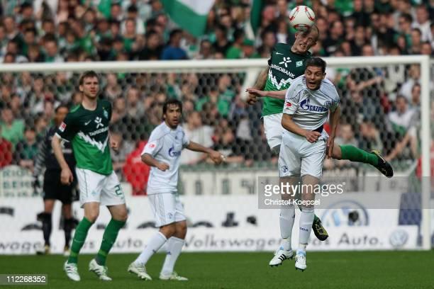 Petri Pasanen of Bremen and Angelos Charisteas of Schalke go up for a header during the Bundesliga match between SV Werder Bremen and FC Schalke 04...