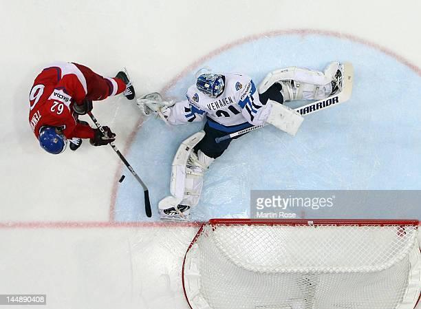 Petri Vehanen , goaltender of Finland makes a save on Petr Tenkrat of Czech Republic during the IIHF World Championship bronze medal match between...