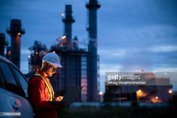 petrochemical engineers work slowly and heavily with smart tablets in the oil and gas industry at night. - gesturing stock pictures, royalty-free photos & images