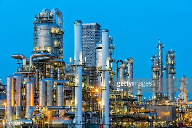 petrochemical plant illuminated at dusk - gas refinery stock photos and pictures