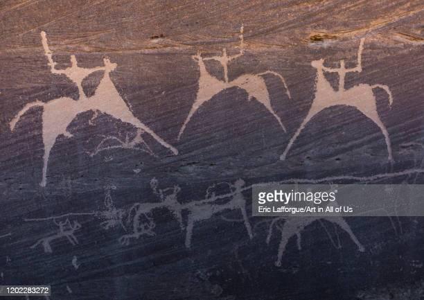 Petroglyphs on a rock depicting men hunting on horses, Najran Province, Minshaf, Saudi Arabia on January 2, 2020 in Minshaf, Saudi Arabia.