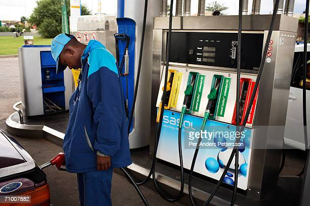 A petrol attendant fuels a customers car at a Sasol station on February 7 2006 in Soweto outside Johannesburg South Africa Sasol makes liquid fuel...