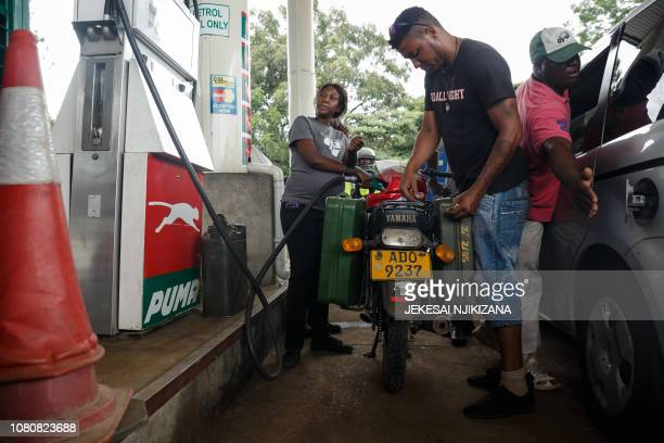 A petrol attendant serves a motorcyclist with two jerry cans attached to his motorbike at a fuel station on January 11 2019 in Harare Motorists are...