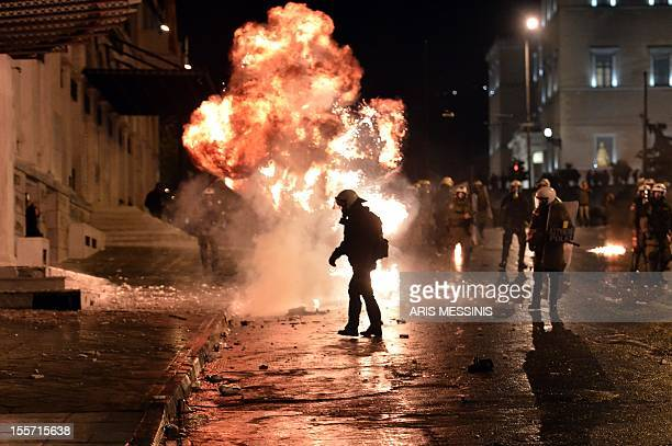 A petrol bomb explodes next to riot police during a demonstration against new austerity measures outside the parliament in Athens on November 7 2012...