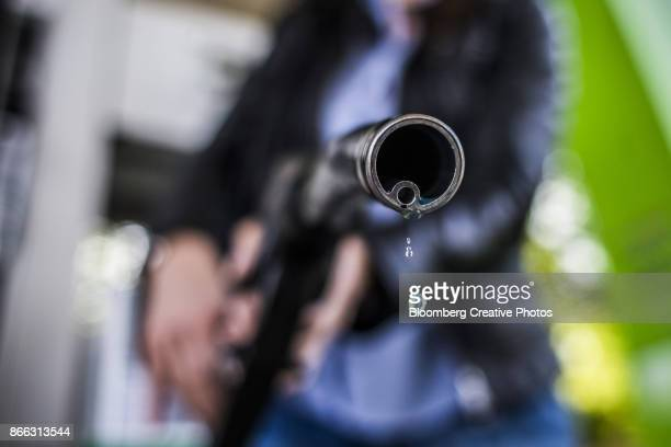 A petrol droplet falls from a fuel pump at a gas station