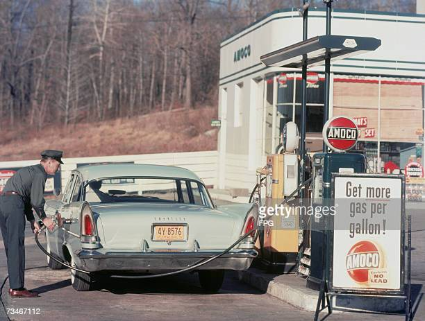 A petrol pump attendant filling up a Chrysler car at an Amoco station 1958