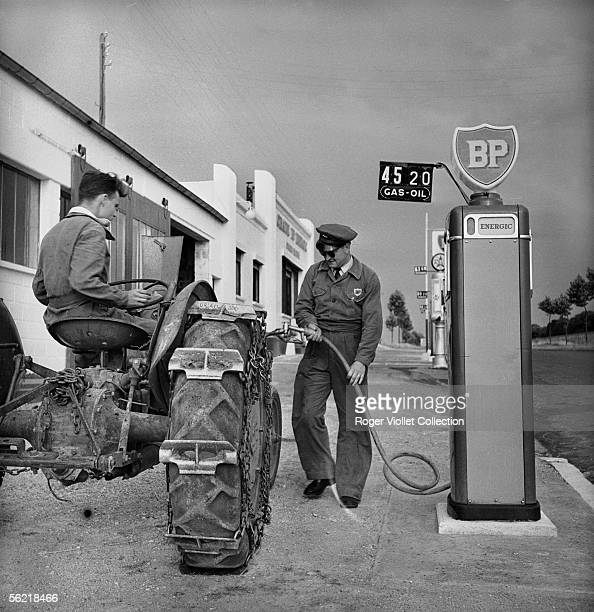 Petrol pump attendant filling up the diesel oil of a tractor in a BP service station France about 1952