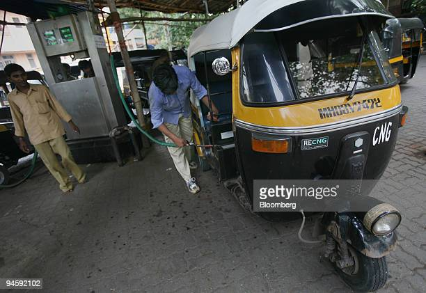 A petrol pump employee fills a rickshaw with Compressed Natural Gas at a gas station in Mumbai India on Monday Sept 10 2007 India's government is...