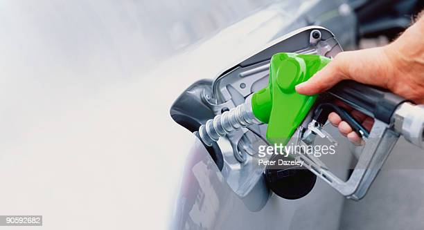 petrol pump filling with unleaded petrol - petrol stock photos and pictures