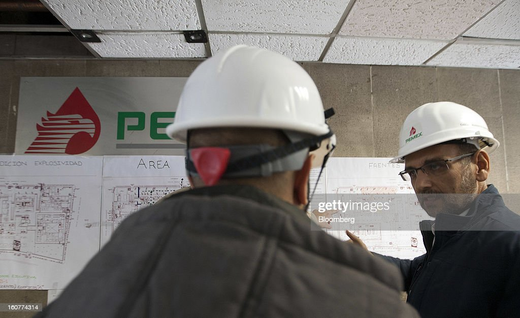 Petroleos Mexicano (Pemex) engineers look at blueprints at the explosion site at the company's headquarters building in Mexico City, Mexico, on Tuesday, Feb. 5, 2013. Mexican authorities said a buildup of gas led to the blast last week that killed 37 people at Petroleos Mexicanos's headquarters, the first official attempt to explain the nation's deadliest explosion since 2006. Photographer: Susana Gonzalez/Bloomberg via Getty Images