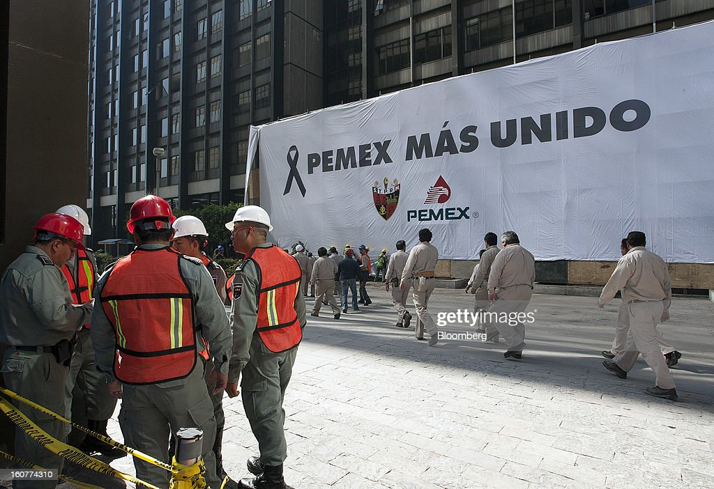Petroleos Mexicano (Pemex) workers walk to the explosion site at the company's headquarters building in Mexico City, Mexico, on Tuesday, Feb. 5, 2013. Mexican authorities said a buildup of gas led to the blast last week that killed 37 people at Petroleos Mexicanos's headquarters, the first official attempt to explain the nation's deadliest explosion since 2006. Photographer: Susana Gonzalez/Bloomberg via Getty Images