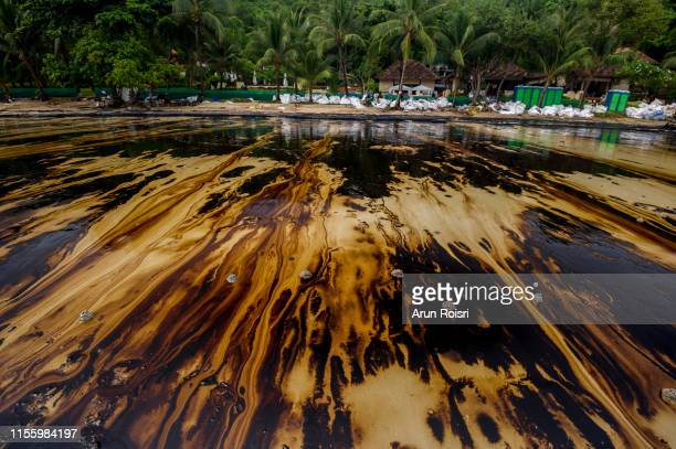 petroleum spill mixed with other chemical substances on sea and sand surface. pollution images, samet island, thailand. - oil spill stock pictures, royalty-free photos & images