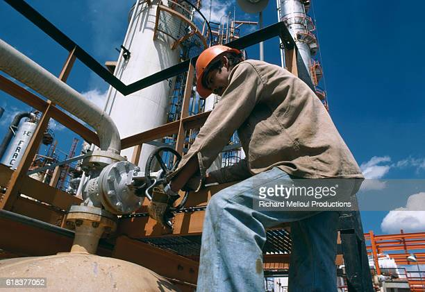 Petroleum worker turning a pipeline wheel at the Pemex oil refinery in Mexico. Pemex is Mexico's national oil refinery.
